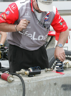 A crew member works on Max Papis' shocks
