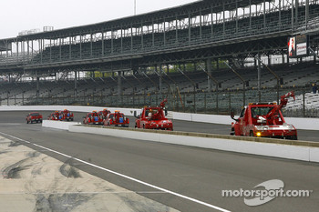 Emergency vehicles circle the Indianapolis Motor Speedway to keep the surface dry as a fine mist falls from the sky
