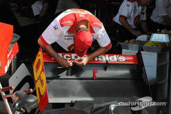 A crew member working on Justin Wilson's rear wing