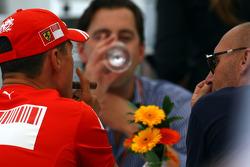 Michael Schumacher, Scuderia Ferrari smokes a cigar in teh Ferrari Hospitality / right: Michel Comte