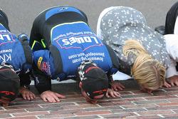 Chad Knaus, Jimmie Johnson and his wife Chandra kiss the bricks