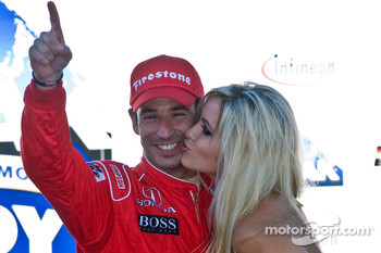 Race winner Helio Castroneves gets a kiss from a lovely Infineon girl