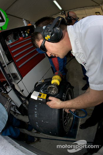 Brumos Racing team member checks tire pressure