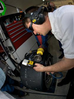 Brumos Racing team member checks tire pressure