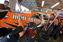 Joe Gibbs Racing Toyota crew members work to repair damage on the car of  Joey Logano