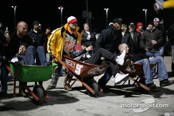 Fans makes a wheel barrow race