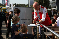 Dr Ullrich, motorsport director Audi signs autographs for the kids in the paddock