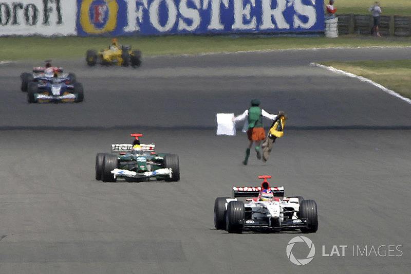 Un hombre pasa frente a los coches en pista