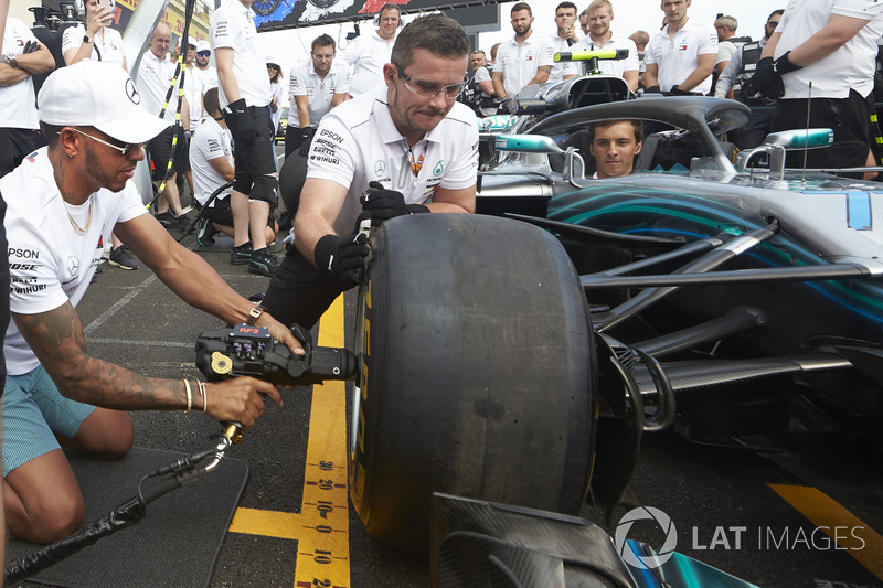 Lewis Hamilton, Mercedes AMG F1, tries his hand with a wheelgun on the car of his team mate