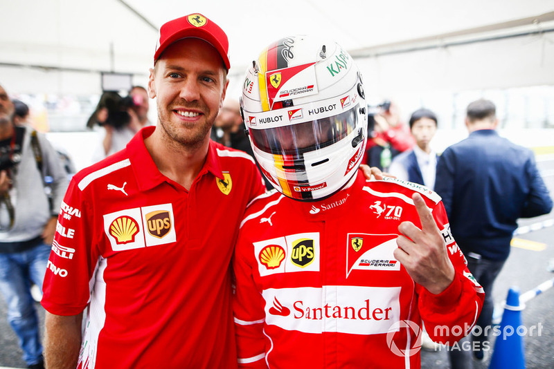Sebastian Vettel, Ferrari, with a fan wearing a replica helmet.