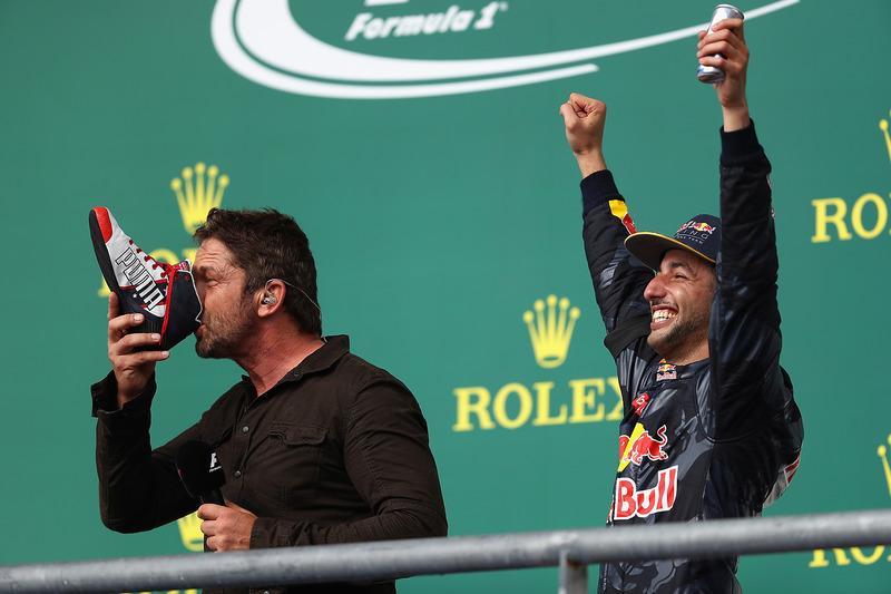 L'acteur Gerard Butler fait un shoey sur le podium avec Daniel Ricciardo, Red Bull Racing, troisième
