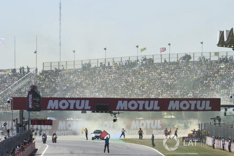 Des fans jettent des fusées de fumée sur la piste au départ