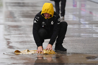 Renault Sport F1 Team mechanic with chamois drying the pit box