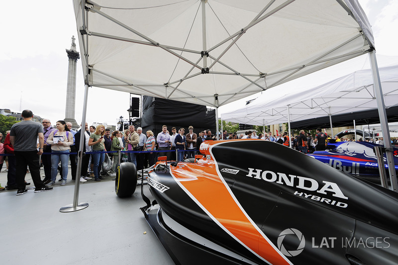 Fans take photos and inspect the McLaren MCL32 on the teams stand