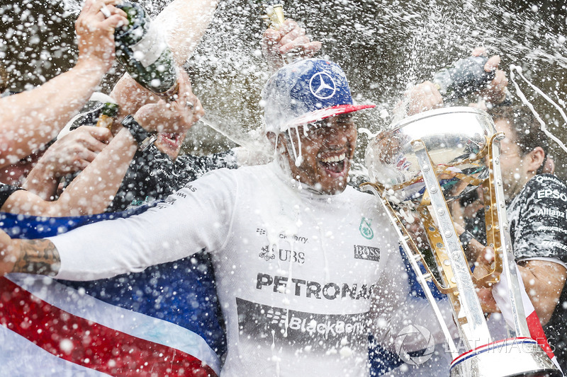 Podium: race winner Lewis Hamilton, Mercedes gets a Champagne soaking from his team after securing a