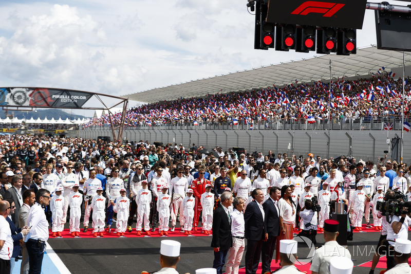 The drivers stand behind the Grid Kid mascots as the national anthem is sung prior to the start