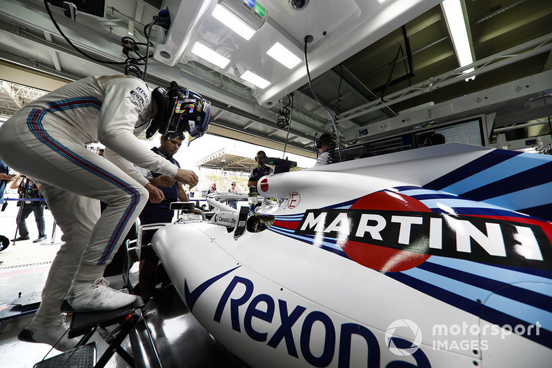 Lance Stroll, Williams Racing, enters his cockpit in the team's garage