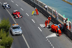 The Renault R24 of Fernando Alonso is recovered by marshalls after crashing out of the tunnel as Michael Schumacher, Ferrari F2004 follows the safety car ahead of Juan Pablo Montoya, Williams BMW FW26