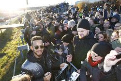 Lewis Hamilton signs autographs