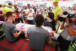 Stoffel Vandoorne, McLaren, and Fernando Alonso, McLaren, sign autographs for fans