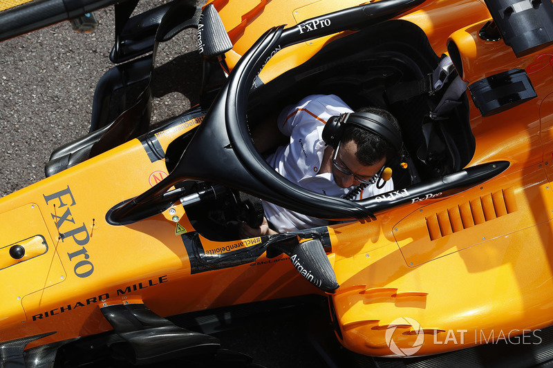 A McLaren mechanic sits in the Fernando Alonso McLaren MCL33 during a practice pit stop