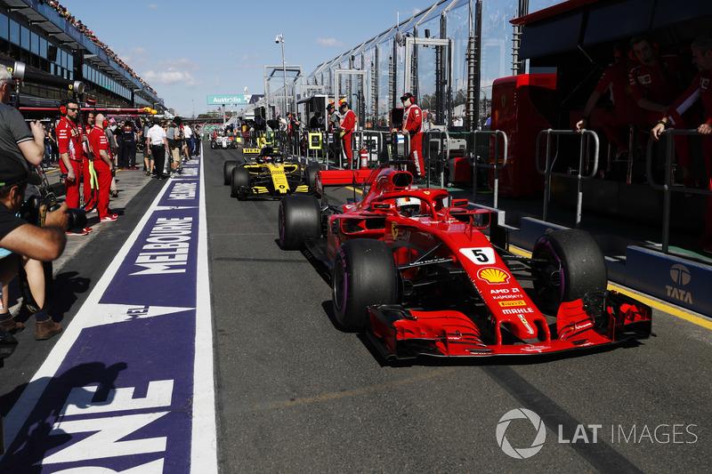 Sebastian Vettel, Ferrari SF71H, leads Carlos Sainz Jr., Renault Sport F1 Team R.S. 18. down the pit