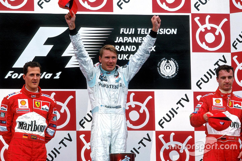 Vencedor da corrida japonesa de 1999 e campeão, Mika Hakkinen, ao lado do segundo, Michael Schumacher e Eddie Irvine, terceiro e vice-campeão