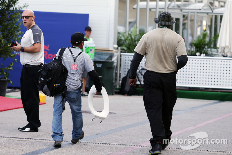 A man with a toilet seat in the paddock