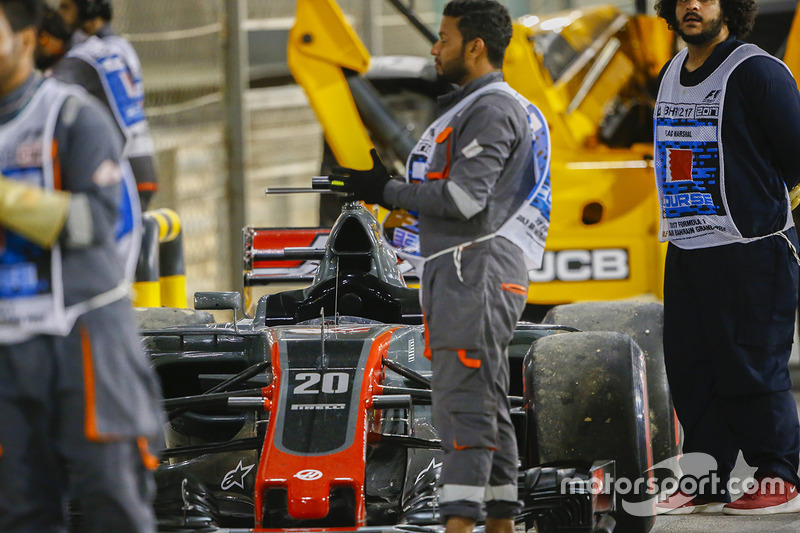 Marshals applaud the drivers on the podium beside the car of Kevin Magnussen, Haas F1 Team VF-17 Fer