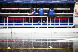 La lluvia cae detrás del equipo de Toro Rosso en la pared del pit