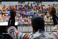 Fernando Alonso, McLaren, waves to fans in a grandstand