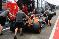 Des mécaniciens McLaren et la McLaren MCL32 dans la ligne des stands