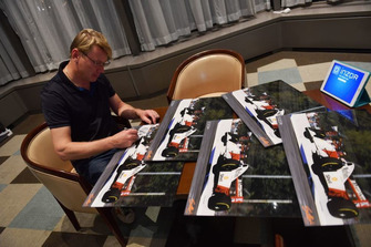 Mika Hakkinen signs his photos from 1993 Australian GP