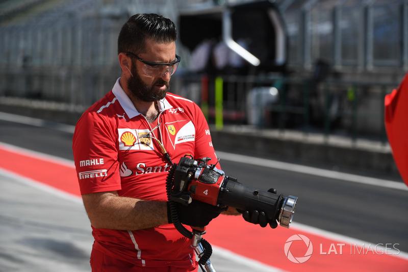 Pistola de rueda y mecánico de Ferrari