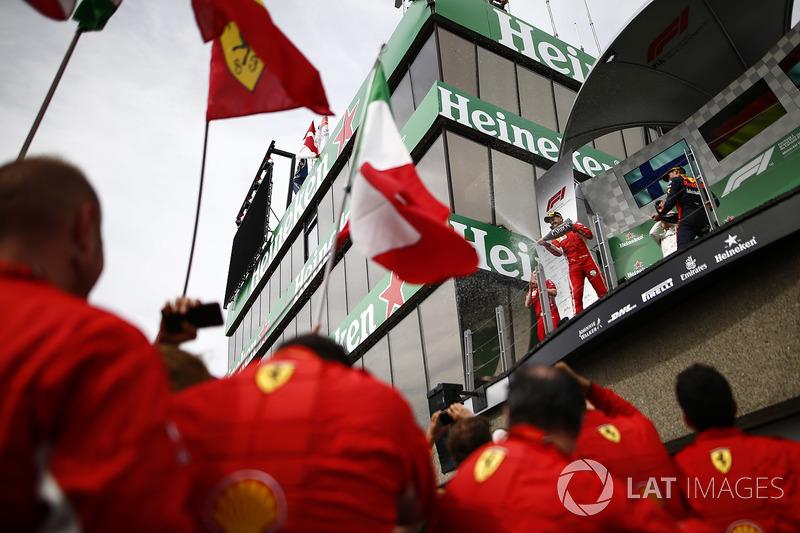 Sebastian Vettel, Ferrari, 1st position, and Max Verstappen, Red Bull Racing, 3rd position, spray Champagne on the podium