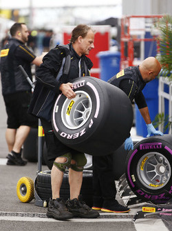 A Pirelli employee manhandles a wheel in the paddock