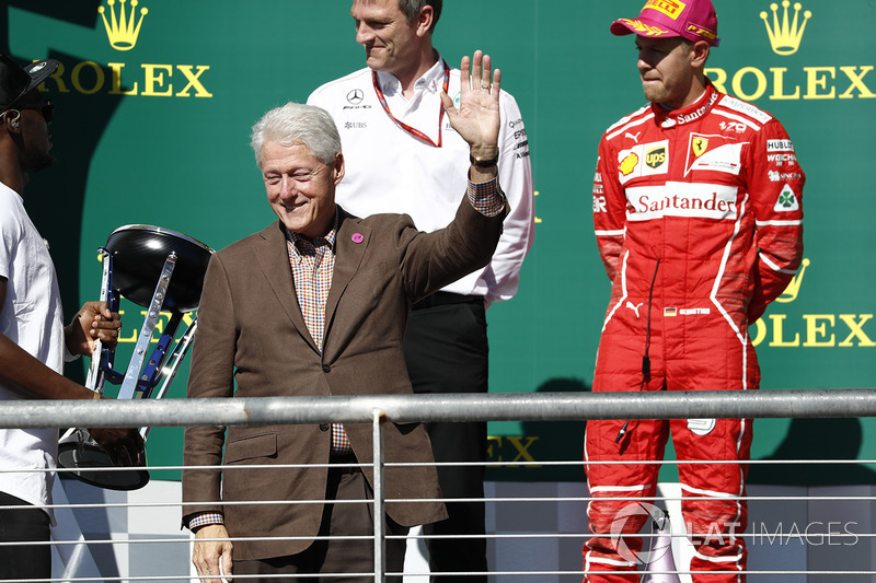 Former US President Bill Clinton alongside Second place Sebastian Vettel, Ferrari, on the podium