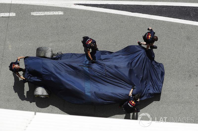 Mechanics push the damaged Daniel Ricciardo Red Bull Racing RB14 under covers in the pit lane
