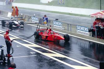 Michael Schumacher, Ferrari F300, con la rueda delantera y el ala faltantes, y David Coulthard, McLaren MP4-13 Mercedes, sin el alerón trasero, en el pitlane