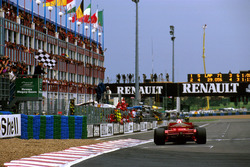 Michael Schumacher, Ferrari F310B, takes the chequered flag