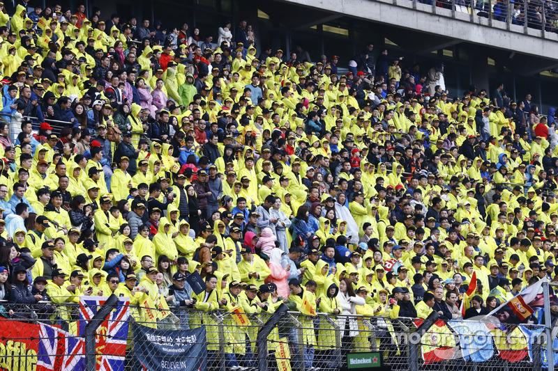Fans auf der Tribüne in gelben Regenumhängen