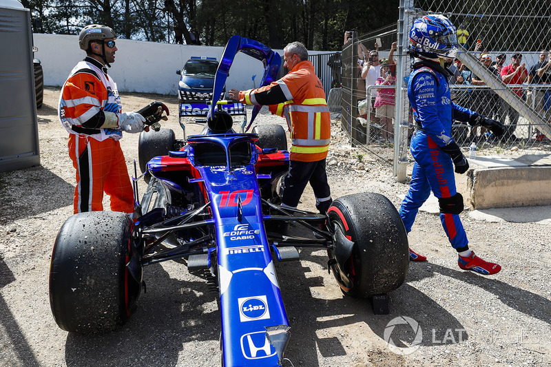 Marshals remove the damaged car of Pierre Gasly, Toro Rosso STR13, as he walks away