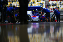 Des mécaniciens Toro Rosso ramènent la voiture de Pierre Gasly, Toro Rosso STR13 Honda, dans le garage