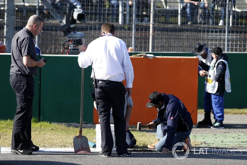 Gli addetti alla pista riparano il circuito
