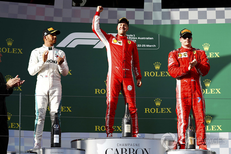 Sebastian Vettel, Ferrari, celebrates victory on the podium with second place Lewis Hamilton, Mercedes AMG F1, and third place Kimi Raikkonen, Ferrari