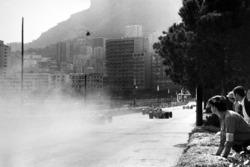 Los coches pasan por el humo del accidente de Lorenzo Bandini, Ferrari 312