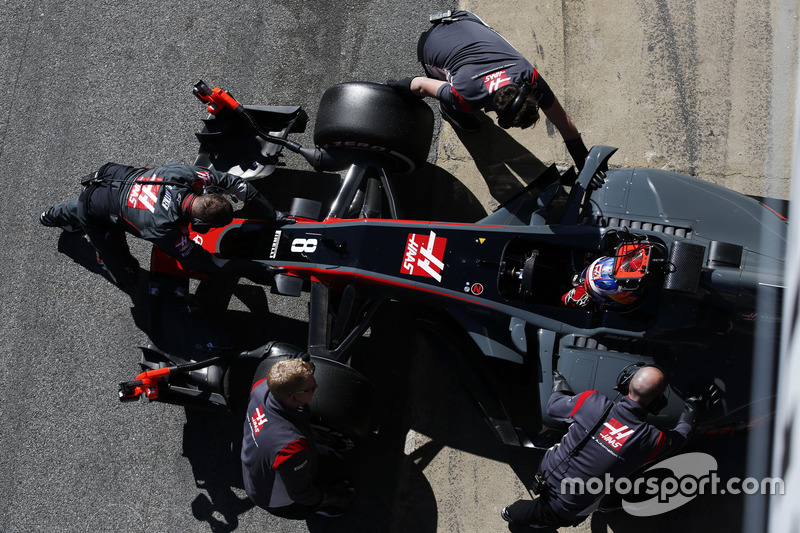 Romain Grosjean, Haas F1 Team, is wheeled into his garage by mechanics
