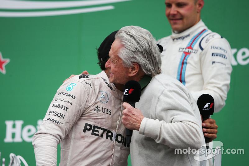 Переможець гонки Льюїс Хемілтон, Mercedes AMG F1, святкує на подіумі з Майклом Дугласом, актором