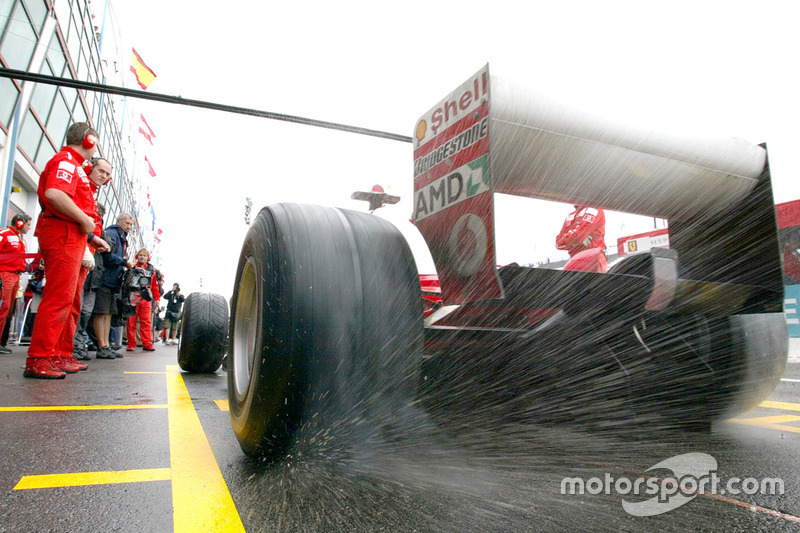 Water sprays from the rear tyres of Michael Schumacher, Ferrari F2003-GA, in the pits