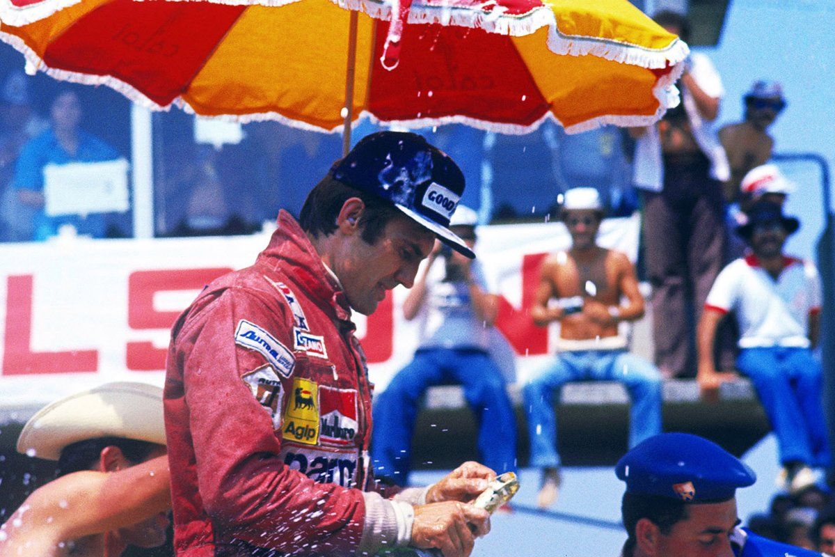 Carlos Reutemann, Ferrari celebrates his victory on the podium attempting to open his bottle of champagne
